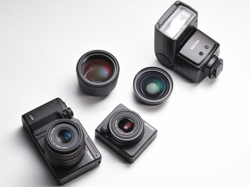 <b>GR LENS A12 50mm F2.5 Macroを装着したGXR(左下)、RICOH LENS S10 24-72mm F2.5-4.4 VC(右下)、テレコンバージョンレンズTC-1(中央左)、ワイドコンバージョンレンズDW-6(中央右)、外部ストロボGF-1(右上)</b>