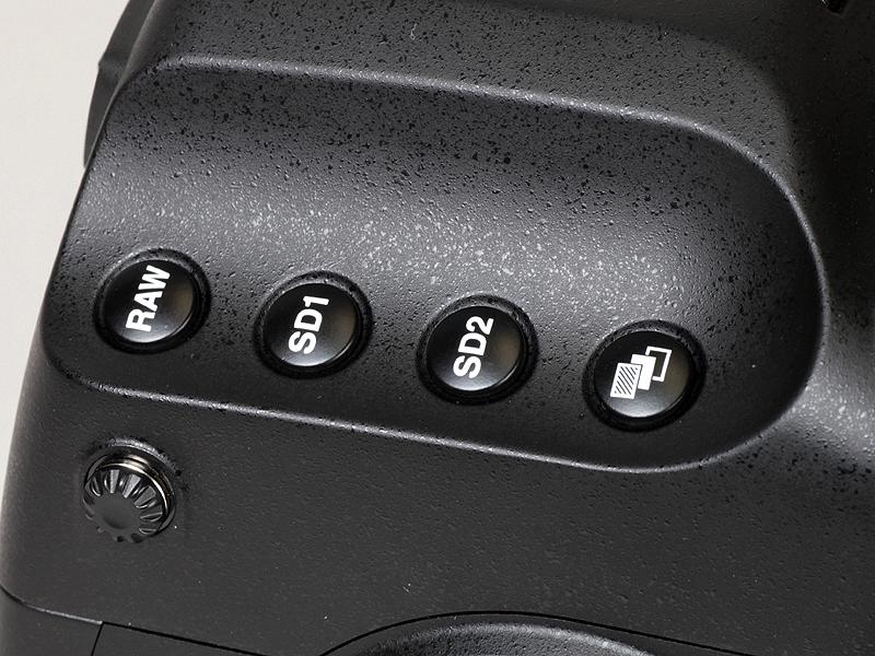 <b>撮影者から見て左側の凹部。中央の2つは、SDスロット1および同2の保存形式設定ボタン</b>