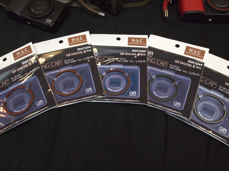 <b>6色のうち当初はフジレッド(左端)が人気だったが、現在はカームブルーが人気らしく取材当日は品切れ。ジーアールシルバー(右端)はカメラ本体のGRロゴに合わせたカラーだという</b>