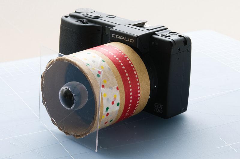 <b>アクリル板に穴を空け、透明球と接着。紙筒とアクリル板も接着剤で貼り付けただけの簡単工作。撮影時にはマニュアルでピントを合わせる。だいたい2cmぐらいの所でピントが合う</b>