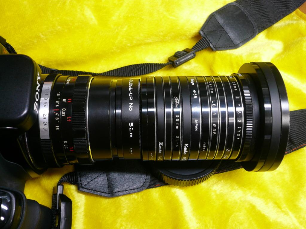 <b>和光のKOBAさんの宙玉レンズ。α100+ペンタコン50mm F1.8に装着。幾重にも連なるのは、ガラスを抜いたフィルターの枠。フィルターの枚数を変えることにより筒の長さが調整できる。中古カメラ店(我楽多屋)で1枚50円で買ったものだそうだ</b>