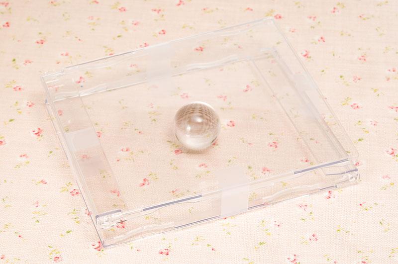 <b>CDケース2つをバラし、透明のビー玉を挟んでテープで留めただけのもの。レンズに装着せずに立てて置いて撮影をしてもいい</b>