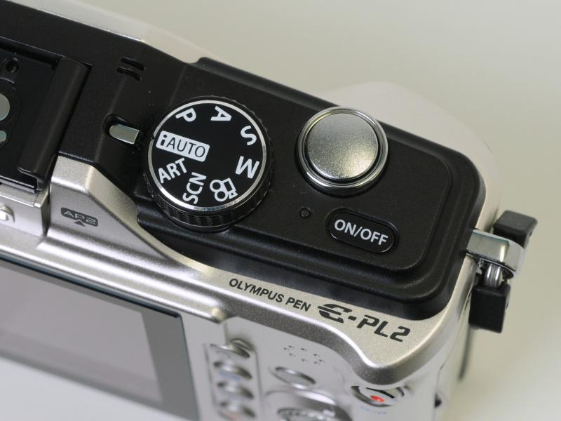 <b>上部右手側の操作部。E-PL1sと同様、電源ボタンとモードダイヤルを右側に配置した</b>