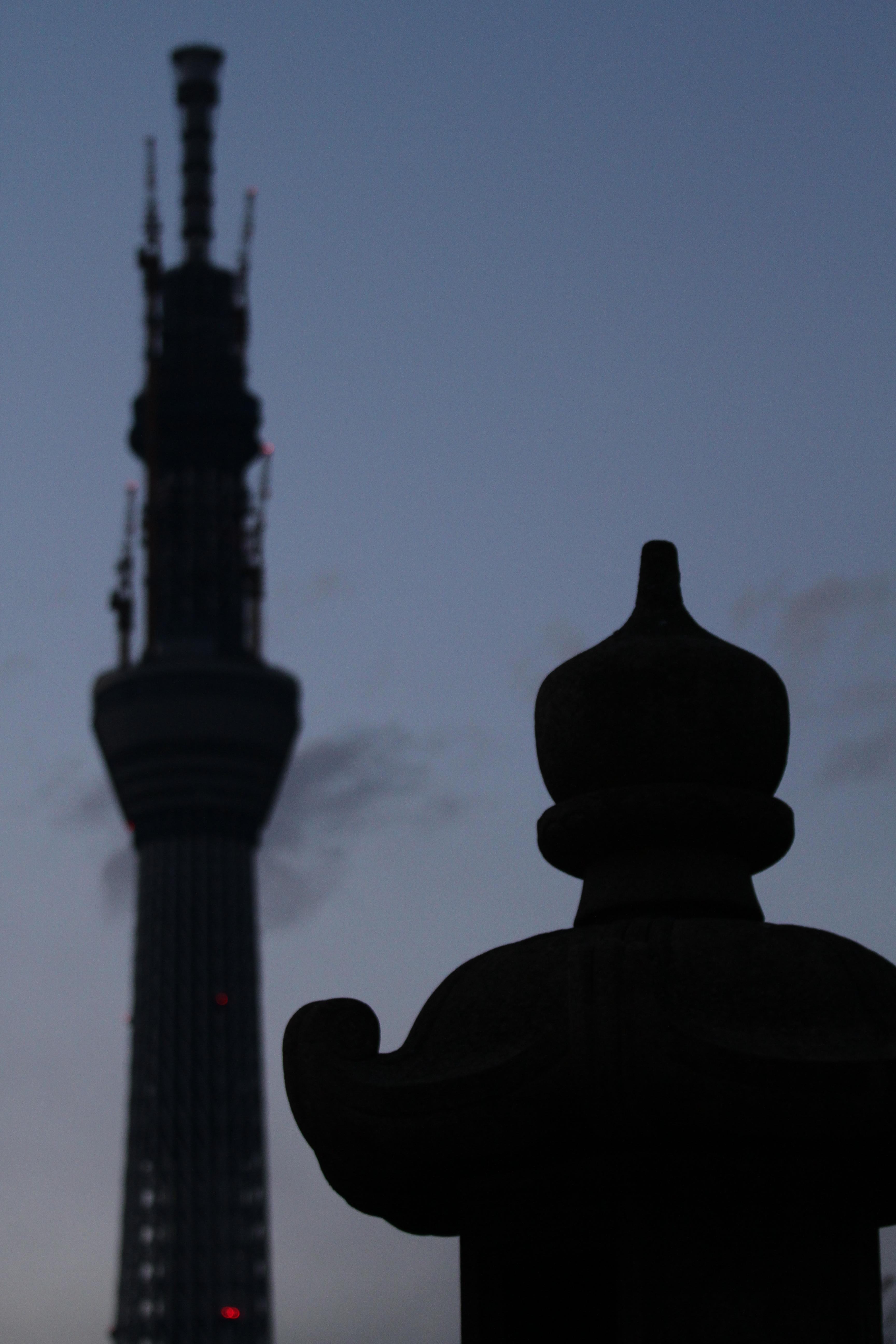 <b>境内の灯篭と東京スカイツリー。なるべくシンプルな写真を狙った。EOS 7D / EF 70-200mm F4 L IS USM / 3,456×5,184 / 1/60秒 / F4 / -1.3EV / ISO800 / プログラム / WB:オート / 78mm / 17:21</b>
