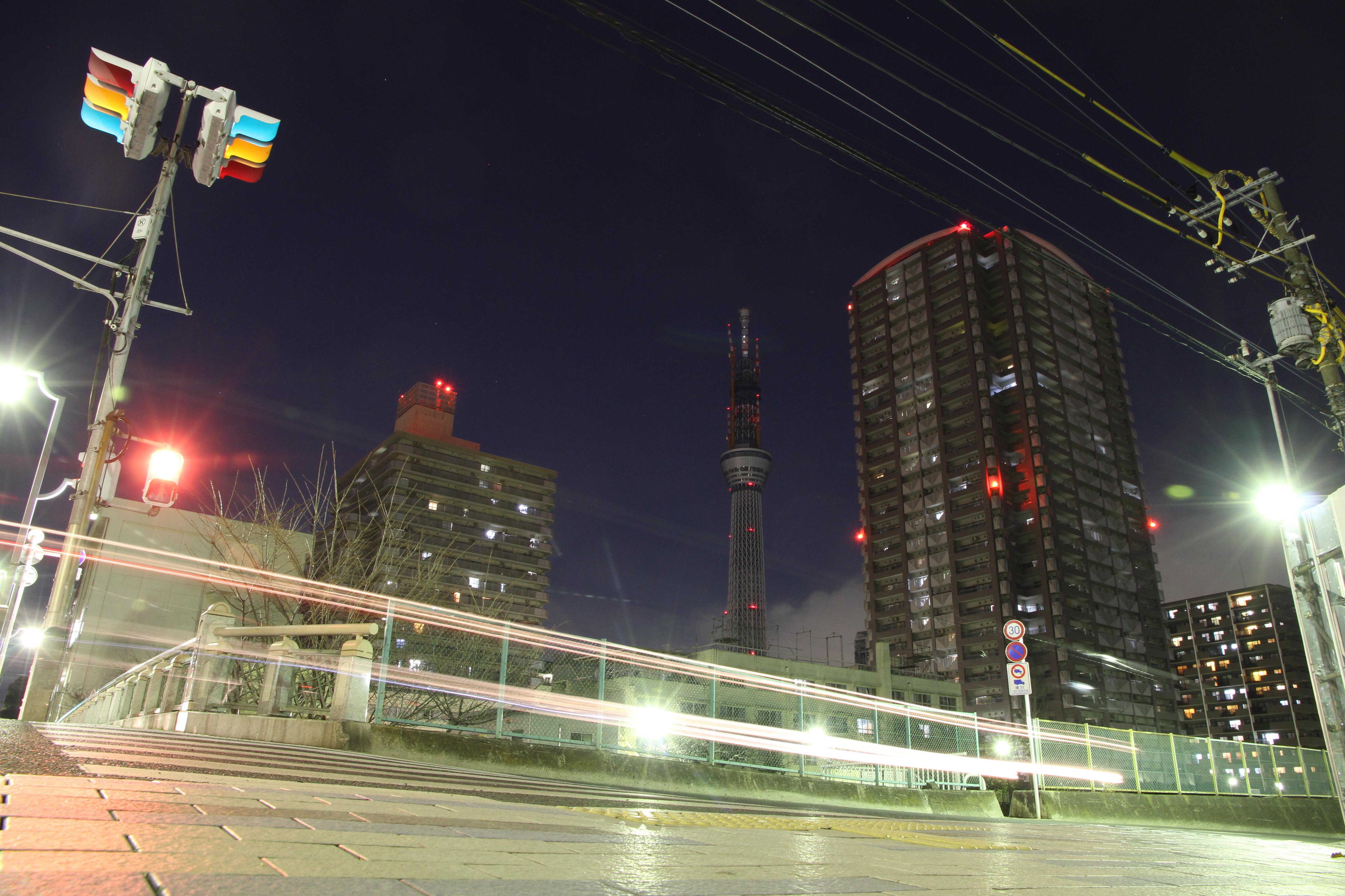 <b>この撮影場所は昼間、工事用車両が出入りしているので夜訪れた。この付近で東京スカイツリーが広く入る位置は少なく、また撮影できるスペースも限られてくる。何度か撮影して10秒間の露光中に信号が3つとも点灯している写真を選んだ。EOS 7D / EF-S 15-85mm F3.5-5.6 IS USM / 5,184×3,456 / 10秒 / F10 / -1EV / ISO400 / 絞り優先 / WB:オート / 15mm / 19:02</b>