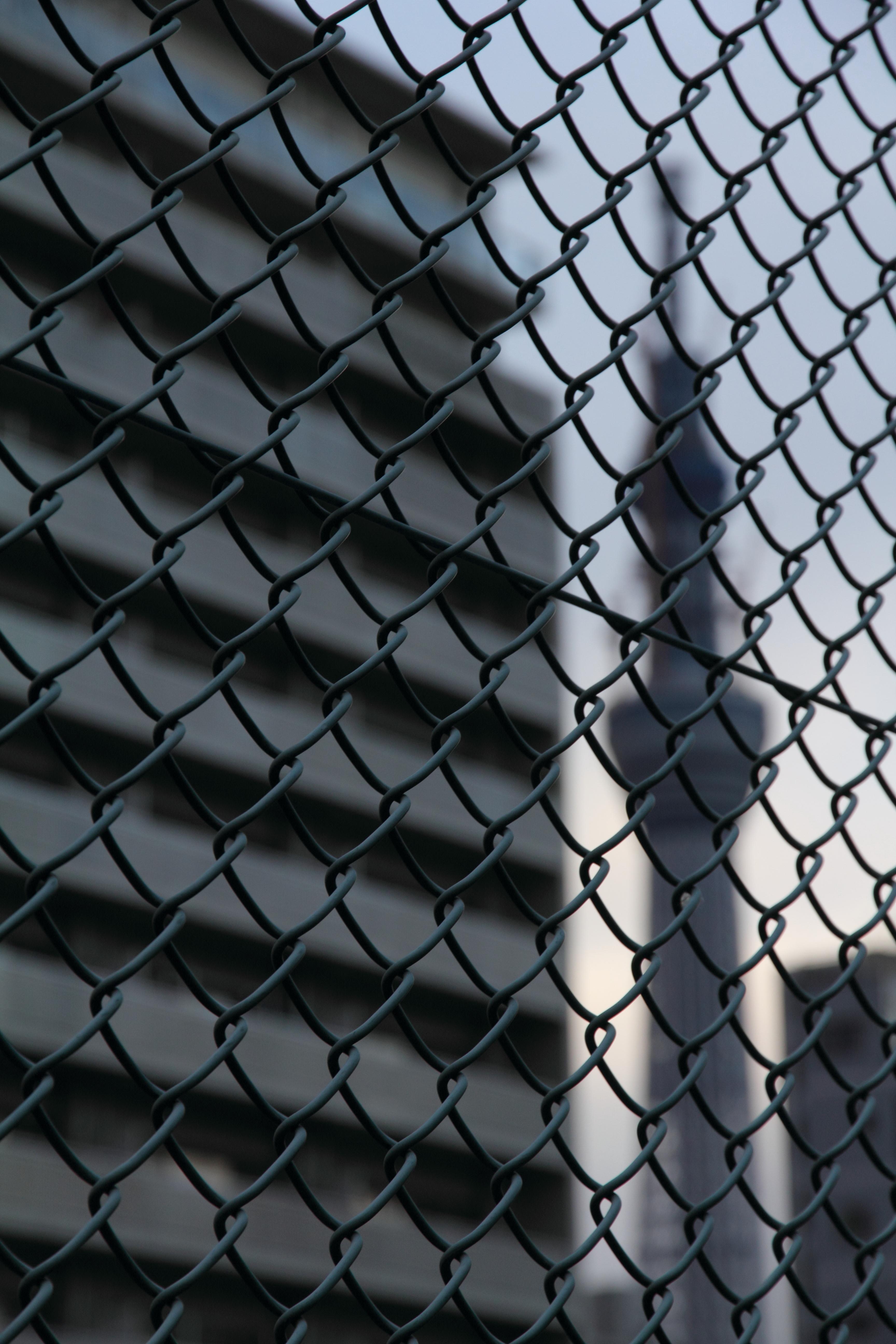 <b>横十間川沿いからも東京スカイツリーは観察できる。ただ、建物などに阻まれ少し撮影はしにくい。ちょうどマンションとビルの隙間から東京スカイツリーが見えるポイントだが、ちょうど網目フェンスが手前にある。近づいて少し望遠で撮影すればフェンスを消すこともできるが、ここではツリーそのもののイメージをなくして撮影した。EOS 60D / EF-S 15-85mm F3.5-5.6 IS USM / 3,456×5,184 / 1/200秒 / F7 / -1EV / ISO250 / 絞り優先 / WB:オート / 76mm / 16:24</b>