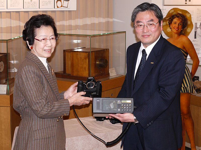 <b>4日に開催した贈呈式では、コダック代表取締役の松浦規之氏(右)が日本カメラ博物館 館長の森山真弓氏(日本カメラ財団 理事長、左)にカメラを手渡した(撮影:豊田堅二氏)</b>