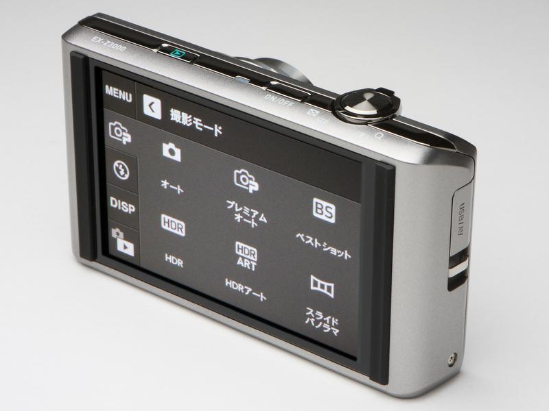 <b>カメラ上部から背面にかけてのボタン、レバー類は最小限といえる。シャッター、電源ON/OFF、再生の各ボタンとシャッターボタンと同軸となるズームレバーがあるのみだ。液晶モニターのサイズは3.2型</b>