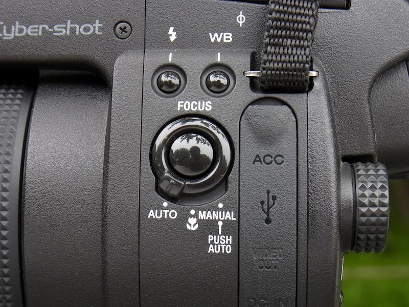 <b>本体側面(左手側)にはFOCUSスイッチがあり、オート(AF)、マクロ、マニュアル(MF)、を切り換える。配置や形状がいいので、ファインダーを覗いた状態で手元を見ずに操作することも可能。ちなみに、マニュアル時に中央のPUSH AUTOボタンを押すと、一時的にAFが作動する。これも便利!</b>