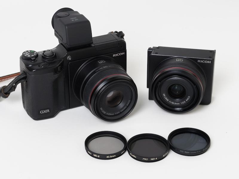 <b>写真奥はGR LENS A12 50mm F2.5 MACROを装着したGXR(左)とGR LENS A12 28mm F2.5(右)。手前左からケンコー「40.5mm PRO ND2」、ケンコー「40.5mm PRO ND4」、マルミ光機「DHGスーパーサーキュラーPLD」(40.5mm)</b>