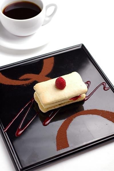 <b>オリジナルメニュー「PENTAX Q SET」1,200円。ラズベリーとバニラ風味のバタークリームを挟んだマカロンケーキ。カカオパウダーで「Q」をデザインしたという</b>