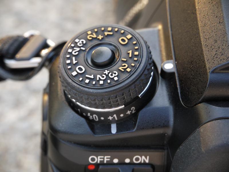 <b>右手側の「露出モードダイヤル」の基部には「ドライブモードレバー」があり、左手側の「露出補正ダイヤル」の基部には「ストロボ調光補正レバー」がある。ちなみに、両ダイヤルにはロック機構があるが、両レバーにはロック機構はない</b>