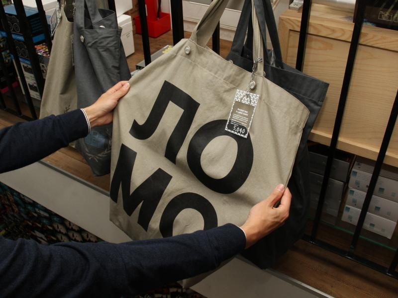 <b>同店でカメラ以外の人気商品というバッグ。写真のモデルはロシア文字の「ロモ」をあしらっている。大きな荷物を持ち歩く専門学校生などが買っていくそうだ。店内にはバッグ以外のアパレルグッズも並んでいた</b>