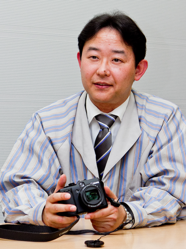 <b>レンズ光学系とファインダーを担当した猿渡浩氏。「特にレンズは製造組立や品質管理の技術がとても大切になってきます。PowerShot G1 Xを世に出すことができたのは、キヤノンのそうした歴史的なDNAとでも言うべきものが非常にプラスに働いて、あらゆるバックアップが有り良いものができたと考えています。カメラのトータルの能力を感じて欲しいと思います」</b>