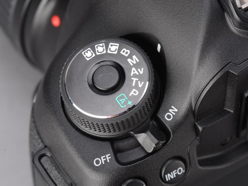 <b>5D Mark IIではサブ電子ダイヤルロックスイッチと兼用だった電源スイッチは、EOS 7Dと同じこの位置に。モードダイヤルは5D Mark IIでは有償でロック付きに改造可能だったが、5D Mark IIIでは最初からロック付きになった。</b>