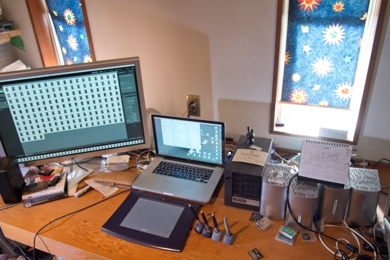 <b>渋谷に近い自宅兼事務所の1Fは所氏の制作のスペースだ。Mac環境をメインにエプソンのA2プリンター、PX-5002やその他のデジタル機器で埋め尽くされ、電源が入りっぱなしなので、熱がこもらないように窓のカーテンはいつも閉まっている</b>