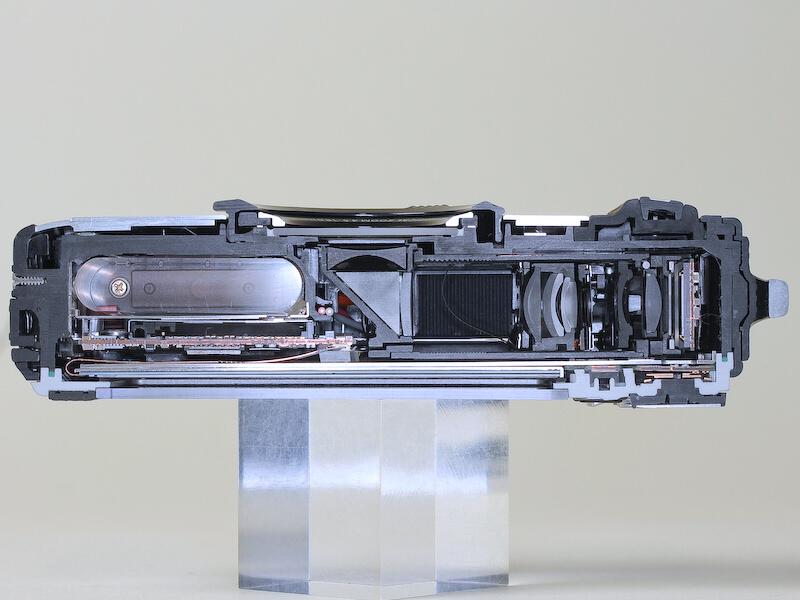 <b>TG-1のカットモデル。屈曲光学系ながら、配置の工夫でレンズ開口部をボディ中央に持ってきている(編集部撮影)</b>
