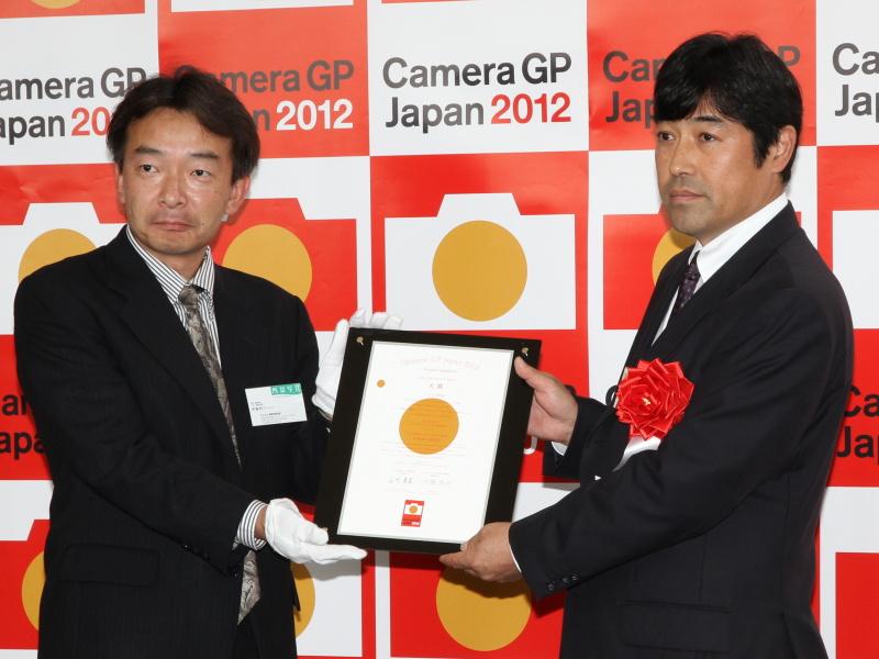 <b>ニコン執行役員 映像カンパニーマーケティング本部長の岩岡徹氏(右)。カメラグランプリ2012実行委員会 委員長の伊藤亮介氏(左)が贈呈した</b>