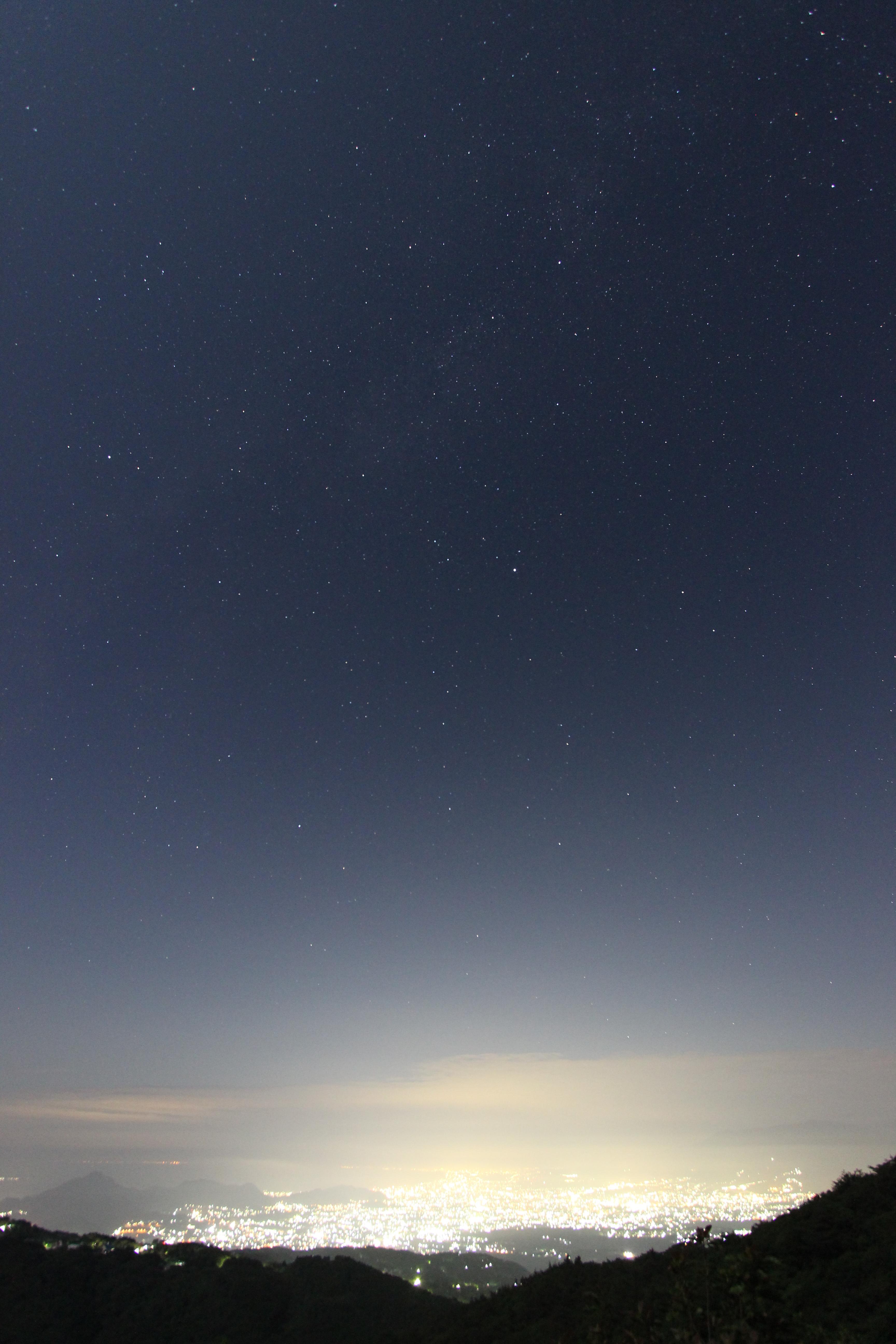 <b>山の高台から遠くの街の夜景と星空を一緒に撮影した。カメラを縦位置にして星空の高さを表現することができた。</b>