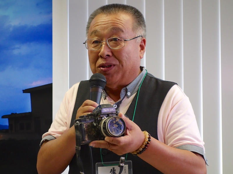 <b>陸前高田市のアマチュア写真家志田信一氏は第3部に参加。手にするのは被災して泥をかぶったニコンF3。カメラ博物館に寄贈される</b>