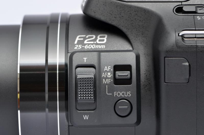<b>鏡筒横にはサイドレバーを装備。前モデルDMC-FZ150にも装備されていたが、DMC-FZ200ではサイズが大きくなり、操作性がより向上している、とのこと。初期設定ではズームの機能が割り当てられているが、セットアップメニューのサイドレバー設定により、MF時のピント合わせやAF時(半押し状態)のピント微調整などが行なえる。</b>