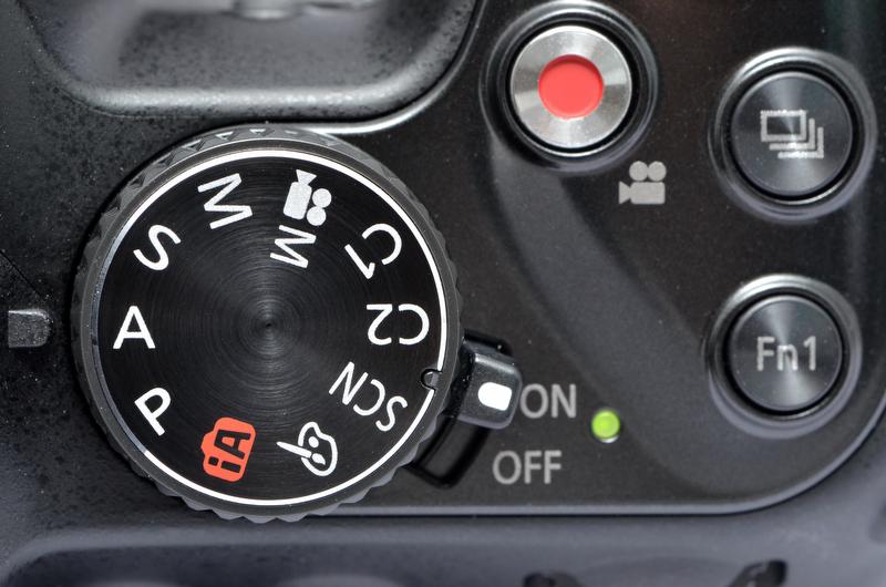 <b>上面のモードダイヤル周辺のボタン配置は、基本的にDMC-FZ150を踏襲している。が、電源スイッチのあった場所にはFn1ボタンが配置され、電源スイッチはモードダイヤル基部に移動した。</b>