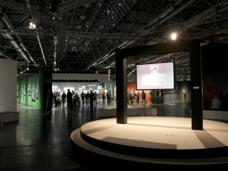 <b>発表などを行なったステージと反対側の様子。多数の写真を展示している。右のスクリーンにはウルライカが3D表示されていた</b>