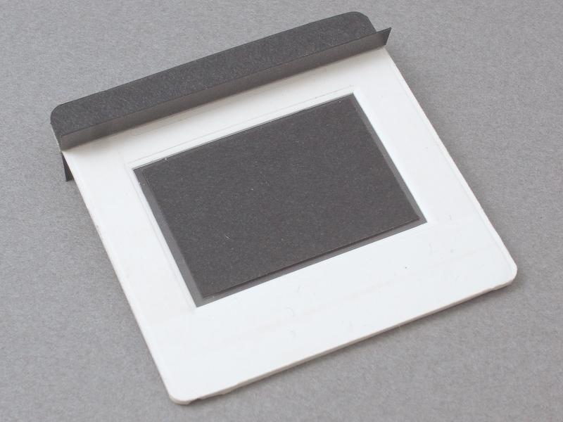 <b>そこで、黒ケント紙をL字に折った遮光パーツを製作し、スクリーン上部に両面テープで貼り付けた</b>