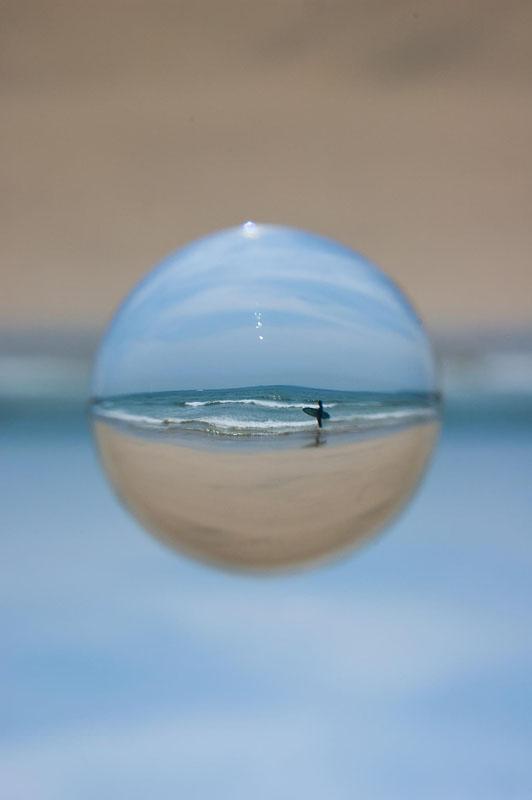 波打ち際でサーフボードを抱えているところ。球の内側と外側で天地左右が反転しているのがよくわかります。ニコンD70、AF-S DX Zoom-Nikkor 12-24mm F4G IF ED