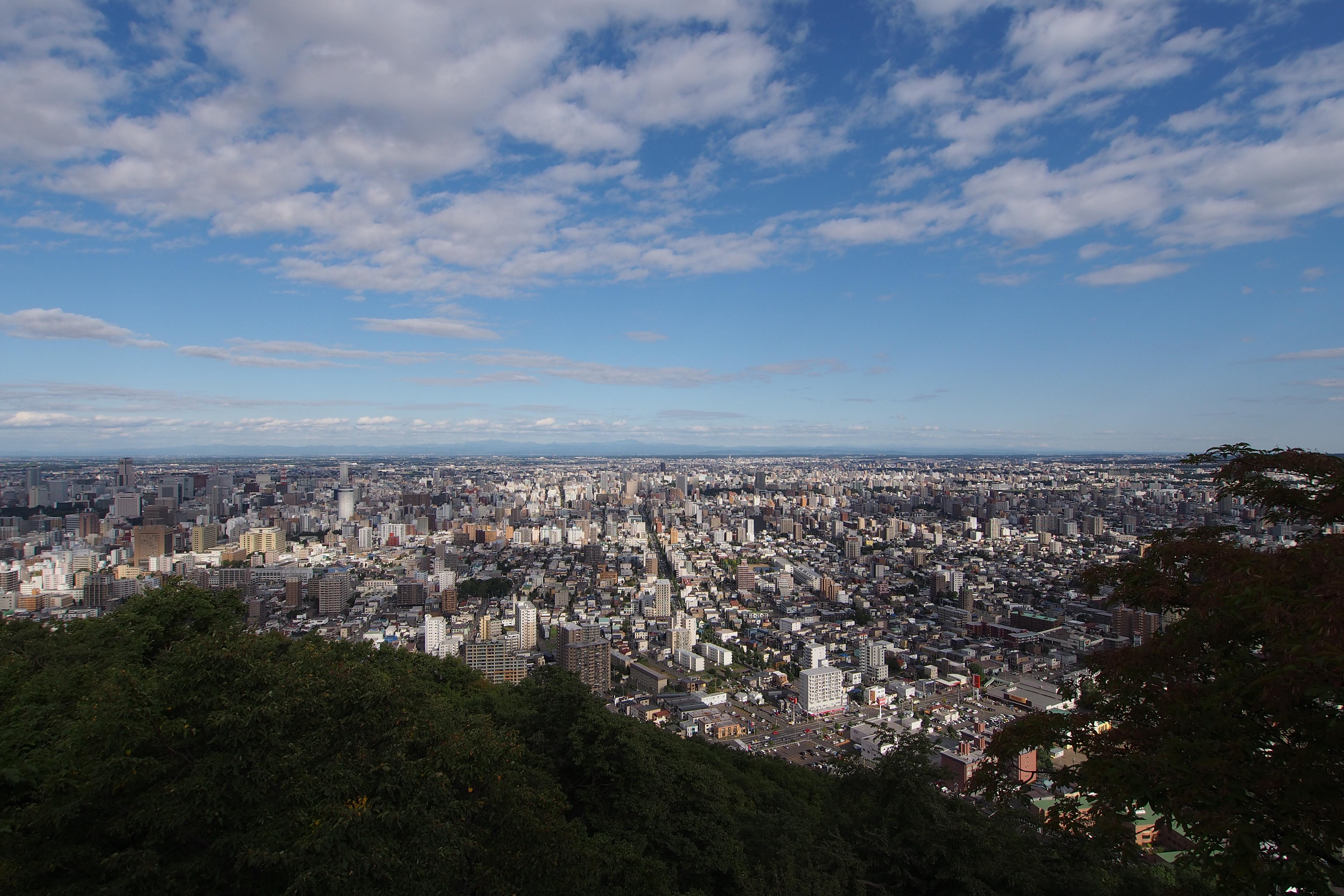 山頂だけ岩場になっていて、札幌市街が一望にできる。標高は225mと低いが、その分短時間で登れるのでお散歩感覚の人も多い。M.ZUIKO DIGITAL ED 9-18mm F4-5.6 / 1/1,600秒 / F5.6 / 0.0EV / ISO200 / 絞り優先AE / WB:オート / 9mm