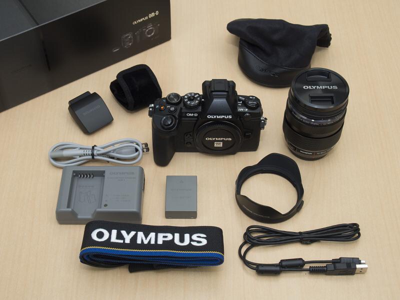 ということで箱の中身の集合写真。E-M1ボディ、リチウムイオン充電池BLN-1、リチウムイオン充電器BCN-1、付属のストロボFL-LM2(布製ケース付き)、USBケーブル、ショルダーストラップ、M.ZUIKO DIGITAL ED 12-40mm F2.8 PRO(レンズポーチ付き)、レンズフードLH-66。