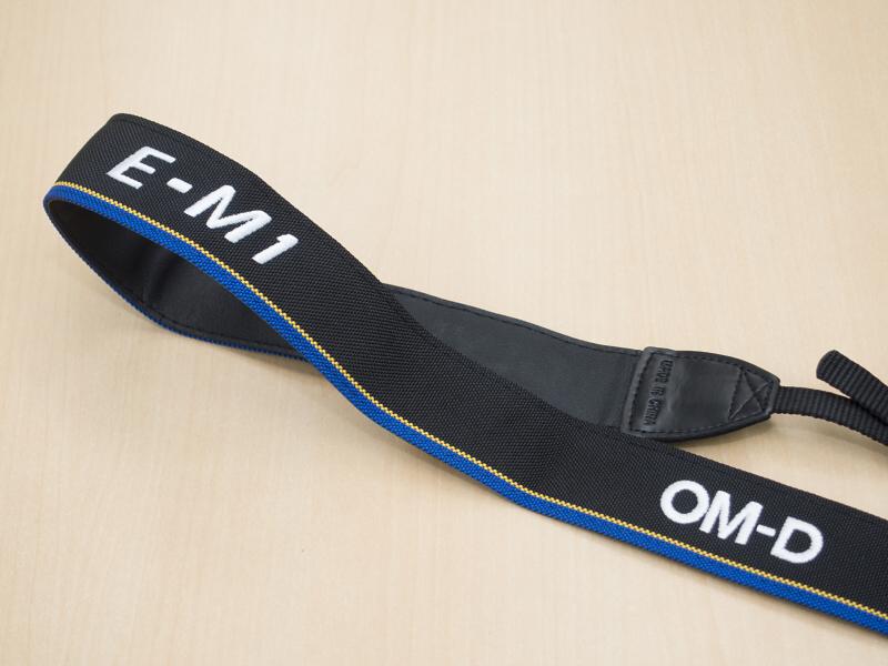 同梱されたショルダーストラップはOM-D E-M1のロゴ入り。幅もこれまでの細身のものから幅広のものに変更されています。