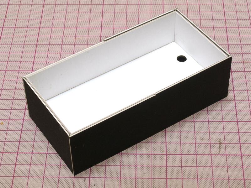 白と黒のイラストボードのパーツを。二重箱の構造に組み立てると、透過光撮影ユニットのボディになる。底板にはiPhone 5のLEDライト用に穴があけられている。接着にはボンドGクリヤーを使用したが、紙はもちろんアクリルなどの樹脂も強力に接着できて重宝する。