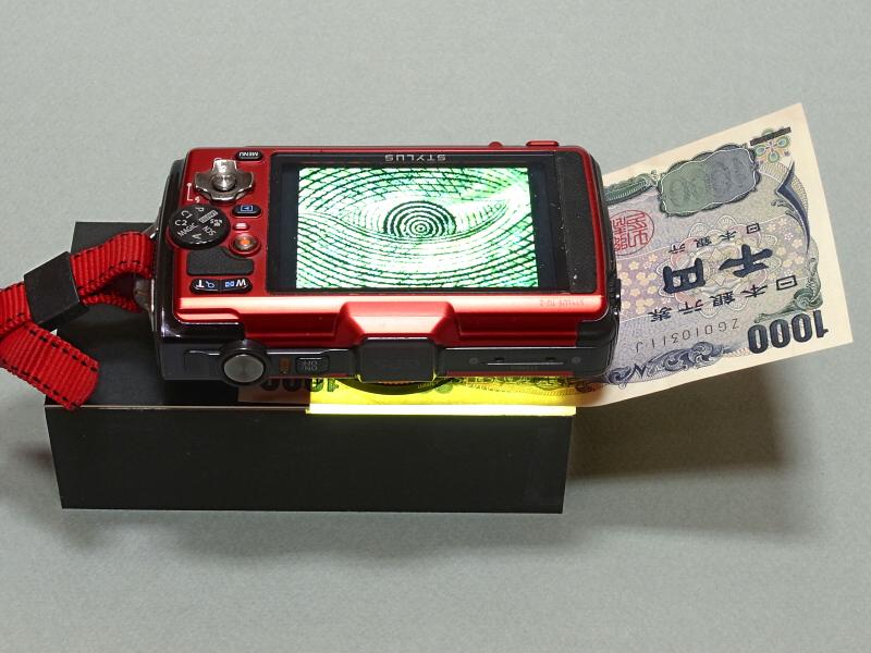 「透過光マクロ撮影ユニット」にTG-2をセットして千円札を撮影していているところ。何か犯罪的な複製装置にも見えてしまうが、そんなことはありません(笑)。