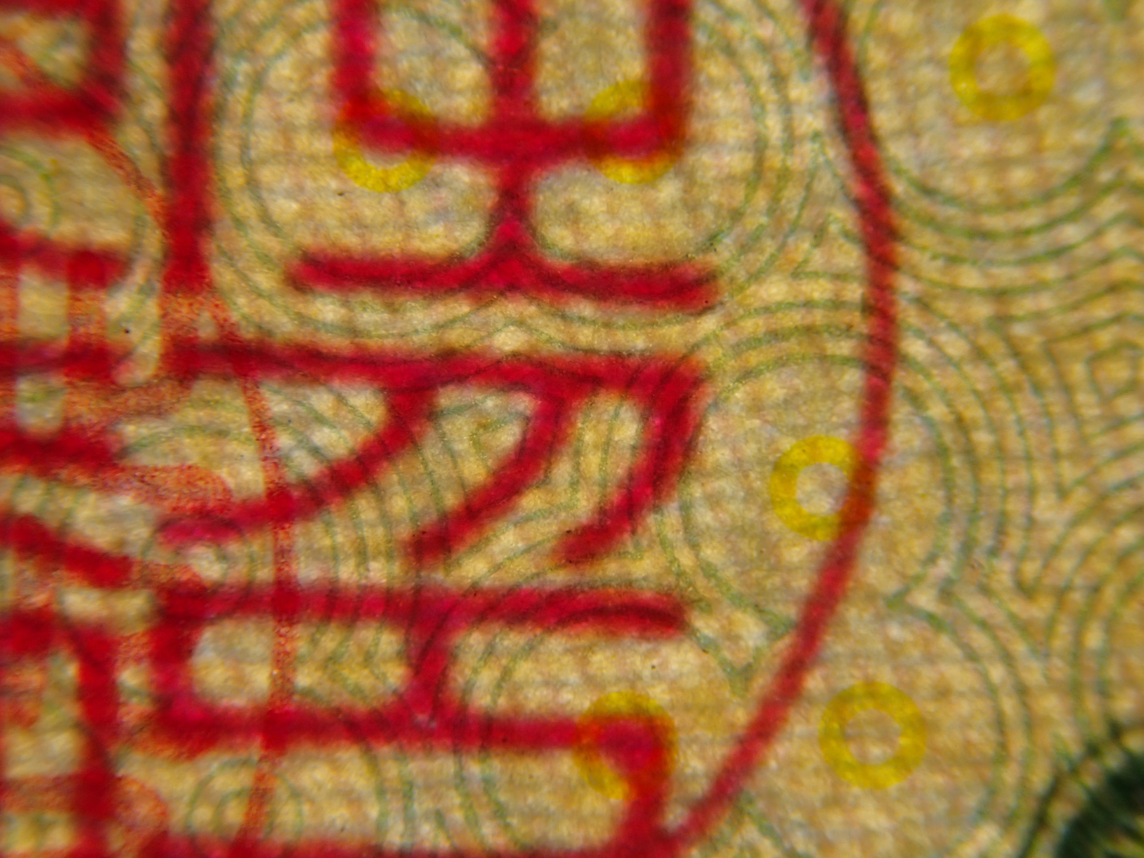 裏面に印刷された渦巻きのような模様と、表面に押された印鑑(総裁之印)の重なり。