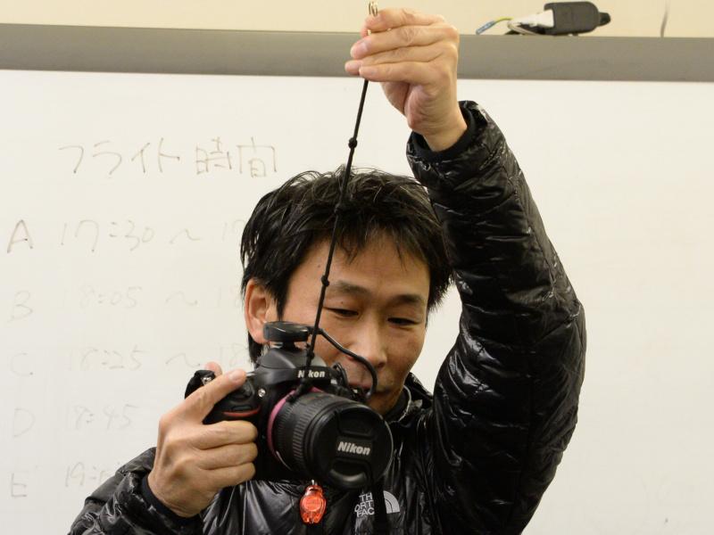 加藤氏の使用機材。撮影位置を記録するためのGPSユニットをホットシューに取り付け、レンズ鏡筒部分をゴムひもで吊ってブレを抑える