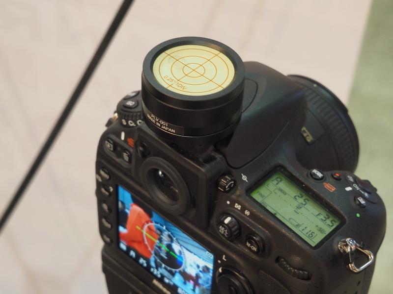 カメラ用精密水準器PLV-001の装着例。0.25度の傾きも計測できるというのが特徴。蓄光機能により、数秒間ライトで照らすとしばらく発光する。本体はアルミ削り出し