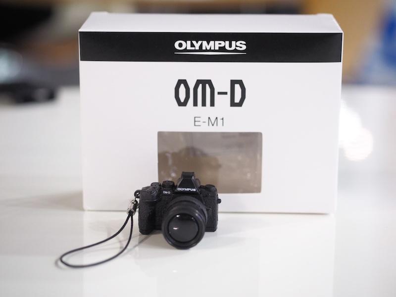 オリンパスブース。オリンパス製カメラを持ってオリンパスブース受付に行くと、「E-M1ミニチュアカメラが付いたオリジナル携帯ストラップ-非売品-」がもらえます。※1人1個まで。なくなり次第終了。