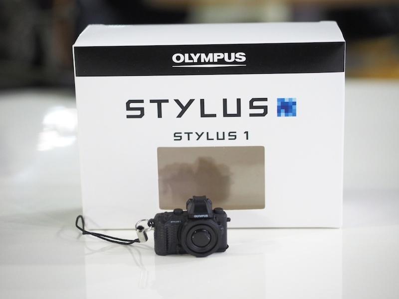 スマートフォンアプリ「OLYMPUS Image Share」をダウンロードして、Wireless(OI.Share)コーナーに行くと「STYLUS1ミニチュアカメラが付いたオリジナル携帯ストラップ-非売品-」がもらえます。※1人1個まで。なくなり次第終了。