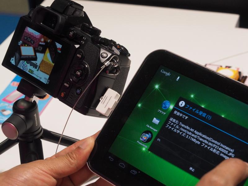 USBアダプターを付けたタブレット端末をカメラのSDカードスロットに近づけると、自動で転送が行なわれる。TransferJetのペアリングは、アプリの設計次第でワンタップかペアリング作業なしで可能だという