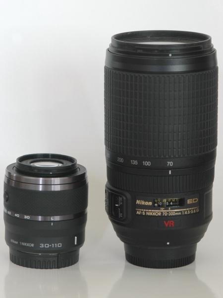 1 NIKKOR VR 30-110mm F3.8-5.6(左)とAF-S VR Zoom-Nikkor 70-300mm F4.5-5.6 G IF-ED(右)の大きさ比較。ほぼ同じ画角の範囲なのだが、画面サイズの違いもあって、Nikon 1用のレンズの方がはるかにコンパクトになっている。