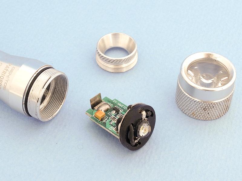 GENTOS PATRIOPRO GT-10AAの先端パーツを外すと、電子回路と一体になったLEDライトが摘出できる。これは電圧を高める昇圧回路で、そのおかげで電池2本(3V)で高照度LEDの発光を可能にしているのだ。