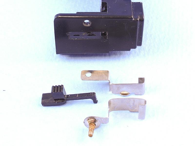 電池レイアウトが決まったところで、電源スイッチについて考えてみる。ご覧の部品はフラッシュバルブ装着金具と排出レバーだが、これをスイッチ金具として流用するアイデアが閃いた。
