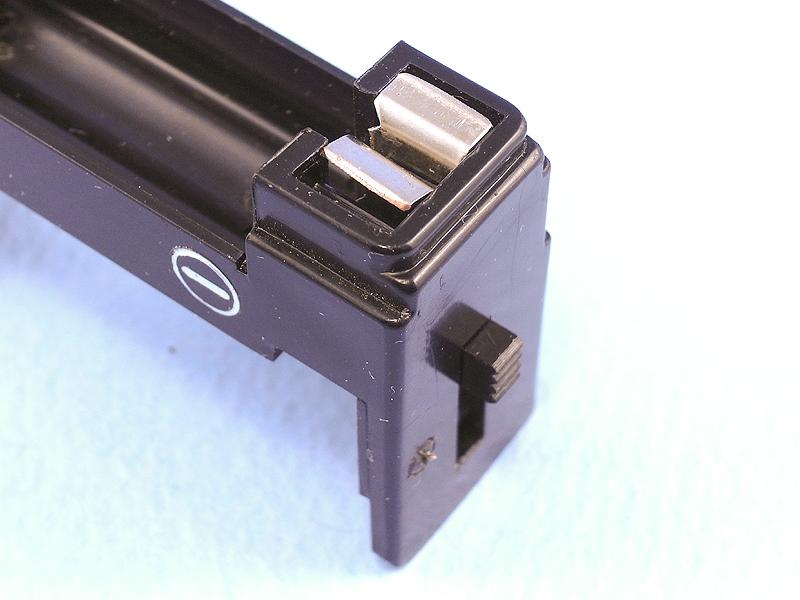 あらためて部品を組み直すとスイッチが完成する。これは電源オフ状態。金具の間にフラッシュバルブ排出レバーが挿入され、隙間ができて通電しない。