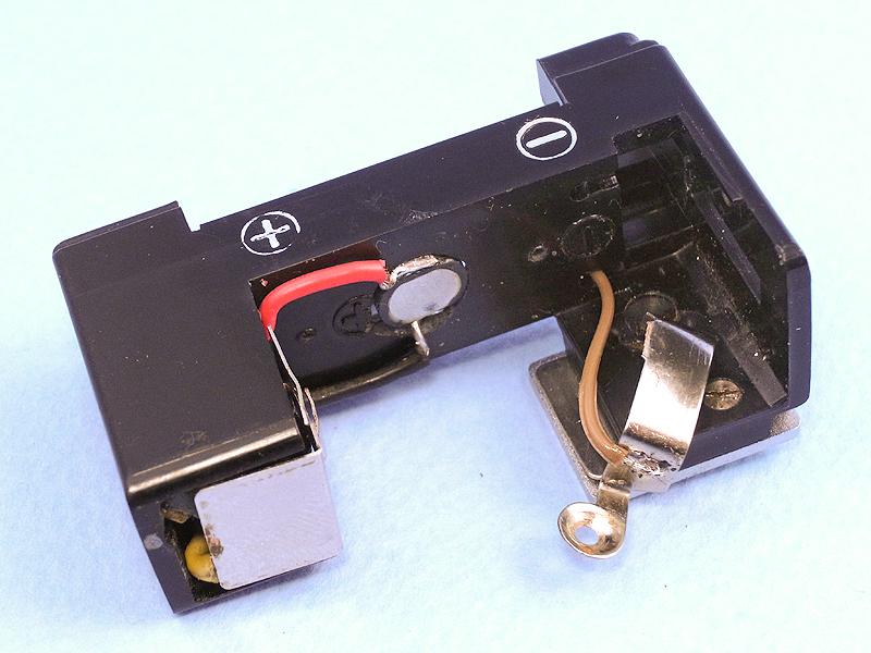 発光部と昇圧回路を再び組み込み、マイナス側の電気接点にコードを半田付けする。コードのレイアウトはあらかじめタイトに決めておかないと、部品が本体からはみ出してしまう。