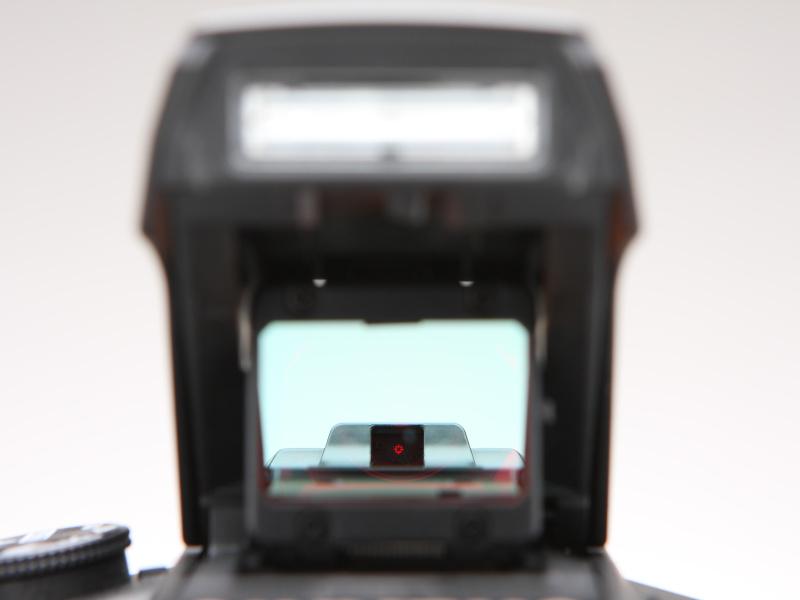 カメラ正面(被写体側)より照準器をのぞく。ハーフミラー越しに赤いレティクル発光部が見える。