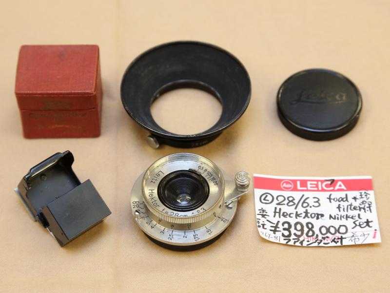 1935年に発売の開始されたヘクトール2.8cm F6.3とフードなどアクセサリー類。ミラーレスでの写りが気になる1本。(千曲商会)