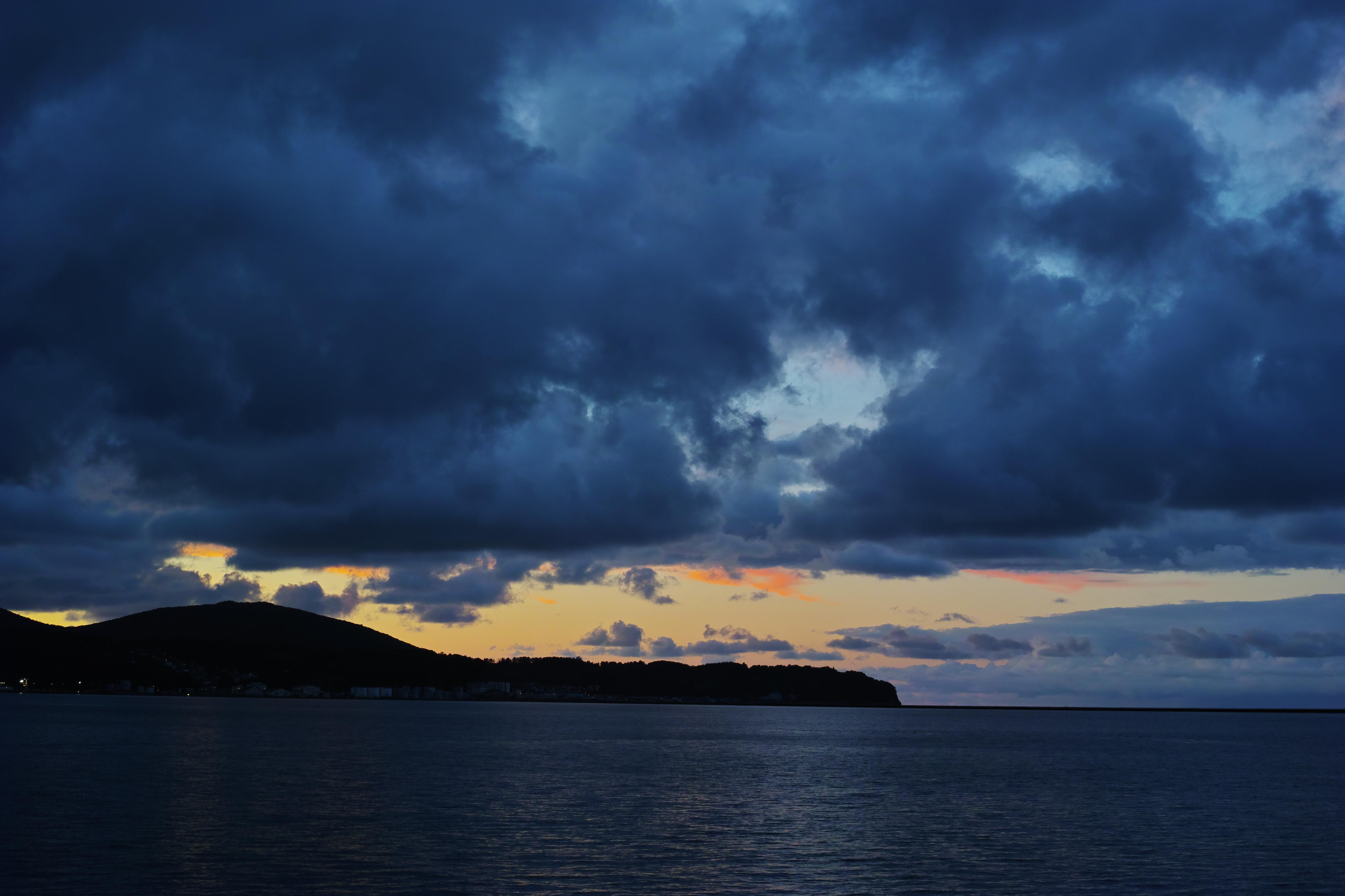 雲間から覗く夕陽。夕闇迫るブルーな世界とぽっかりと空いたオレンジ色の夕焼けの深く濃い色合いが郷愁を呼び覚ます。ISO100 / F5.6 / 1/15秒