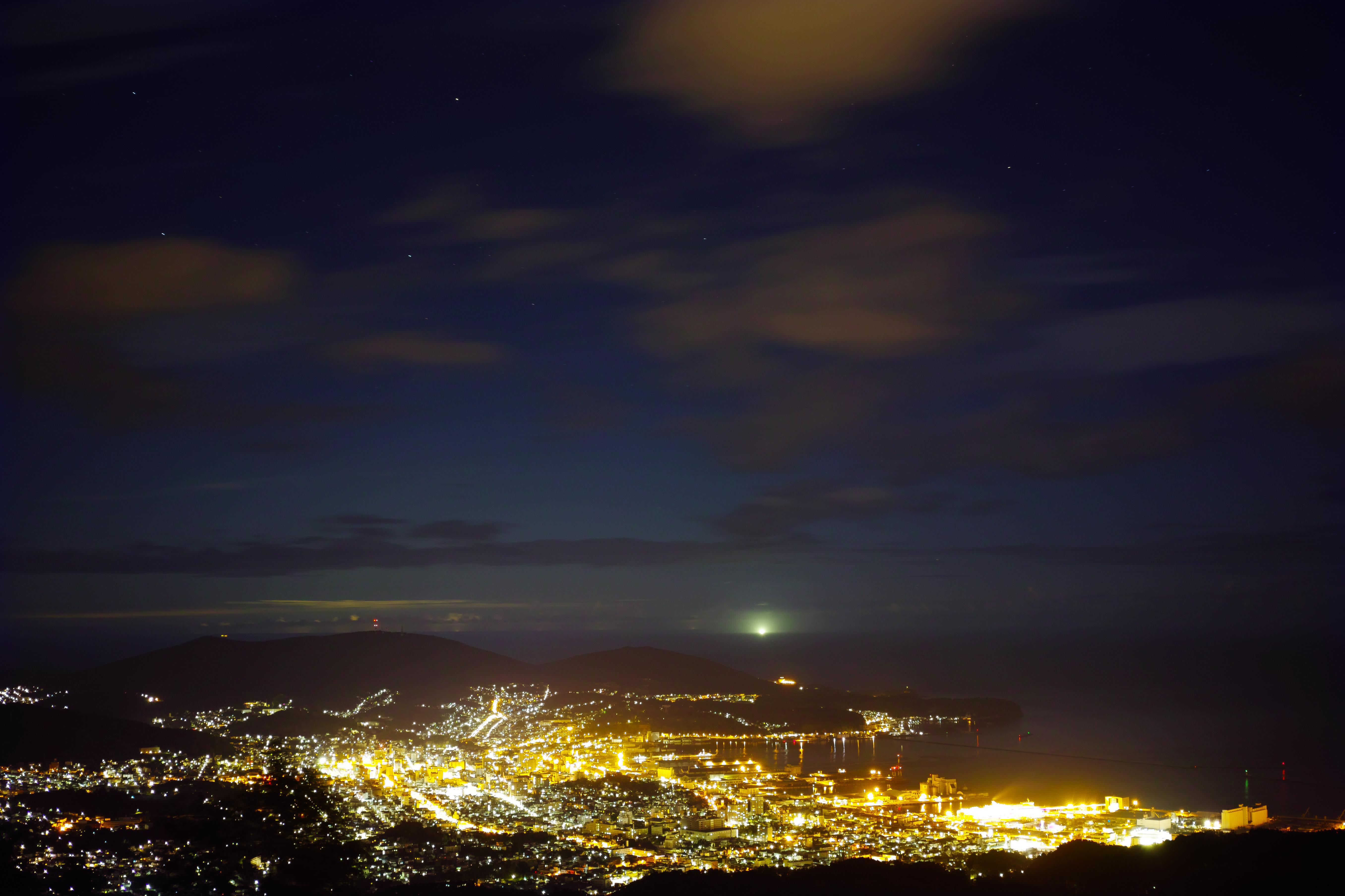 山腹より望む街の夜景と星空。暗い空の下、煌びやかな街の明かりが人の息づかいを感じさせる。ISO100 / F2.8 / 30秒