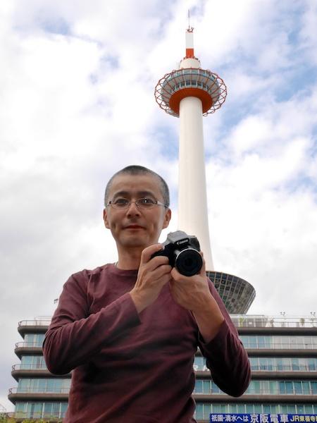 京都タワーを前に、PowerShot SX60 HSと川北茂樹さん。果たしてどんな写真が撮れるのか?